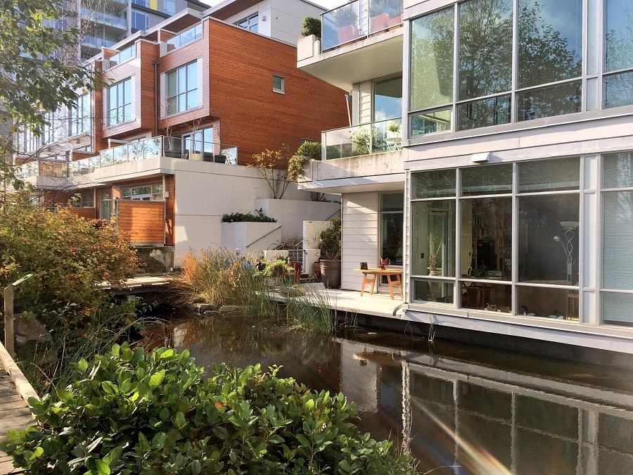 An idyllic urban setting shows the courtyard of Dockside Green with pond and a number of balconies overlooking.