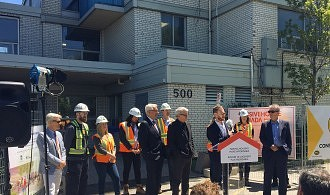 ERA Principal Graeme Stewart addresses a crowd in front of Ken Soble Tower alongside MP Adam Vaughan during the May 21, 2019 National Housing Strategy announcement.